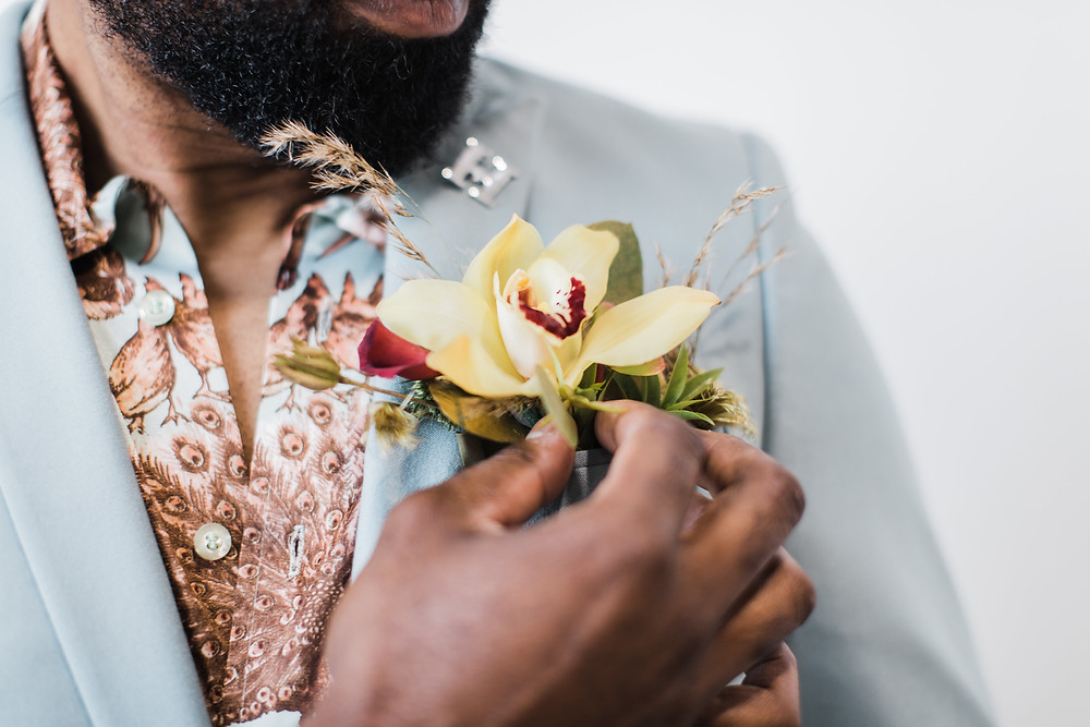 as an alternative to a traditional boutonniere, a floral pocket insert compliments the groom's unique look