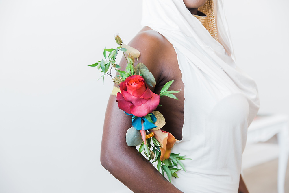 a unique floral piece attached to the bride's arm