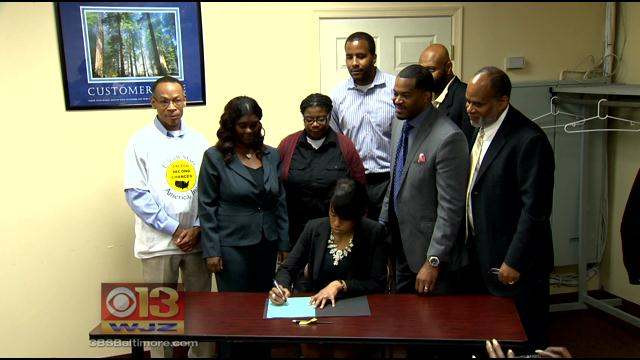 Baltimore community members standing around Baltimore mayor Stephanie Rawlings Blake as she signs Ban the Box legislation into law
