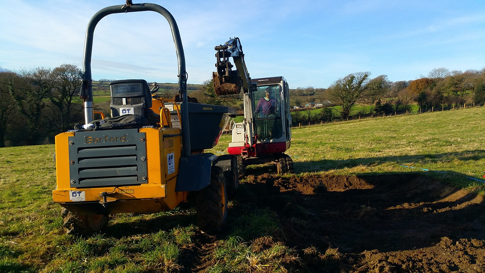 Dumper truck and digger creating a shallow trench