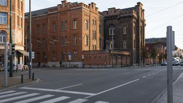 3 octobre 2017, Buxelles.   Ce centre d'accueil est dirigé par l'agence gouvernementale Fedasil, il est très visible, massif, imposant, il se détache très nettement de son environnement ; c'est le premier centre de demandeurs d'asile à ouvrir en Belgique, en 1986 et également le premier de part sa capacité d'accueil, un peu plus de 800 places. De l'extérieur, un imposant drapeau l'identifie sans ambiguïté, l'entrée est bornée par une porte massive, un poste d'accueil immense surveille les entrées et les sorties de nombreuses personnes.