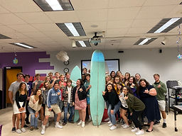 group of Leardership students posing wirh surfboards