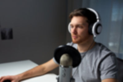Man listening to music. Sitting in front of a microphone.