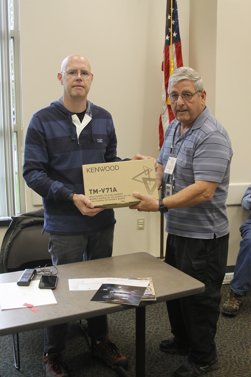 Jim Harrigan (left) receives his new radio from VE Examiner Dave Williams, N2VLQ