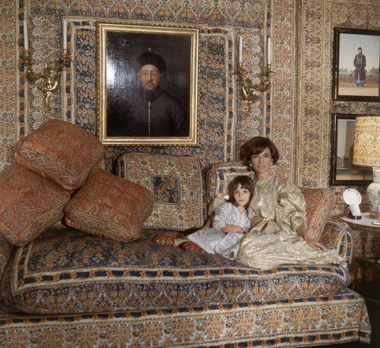 """(""""Mrs. Radziwill, wearing a caftan that was a gift from Hassan II of Morocco, and her daughter, Tina, nestle on a divan that Mongiardino installed at one end of the drawing room. Indian printed cottons were used for the rooms' walls and curtains, the divan's upholstery, and lampshades. Photo: Cecil Beaton."""" Inside Lee Radziwill's legendary London home, fashioned by Renzo Mongiardino. Architectural Digest.)"""