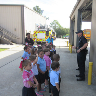 Captain Ricky is showing the children where the fire trucks are maintenanced at the Main station.