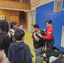 Firefighter Amber lets the local children try on the equipment.