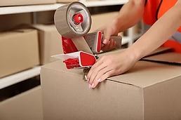 Person Taping Box at Warehouse.webp