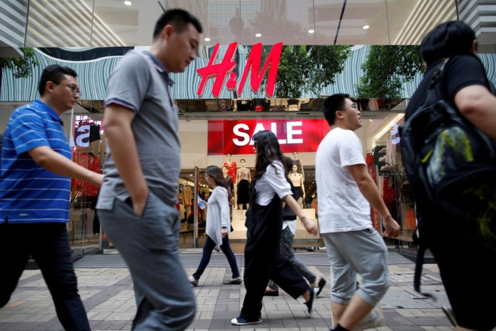 FILE PHOTO: People walk past a H&M fashion chain store at Tsim Sha Tsui shopping district in Hong Kong, China August 1, 2016. REUTERS/Tyrone Siu/File Photo