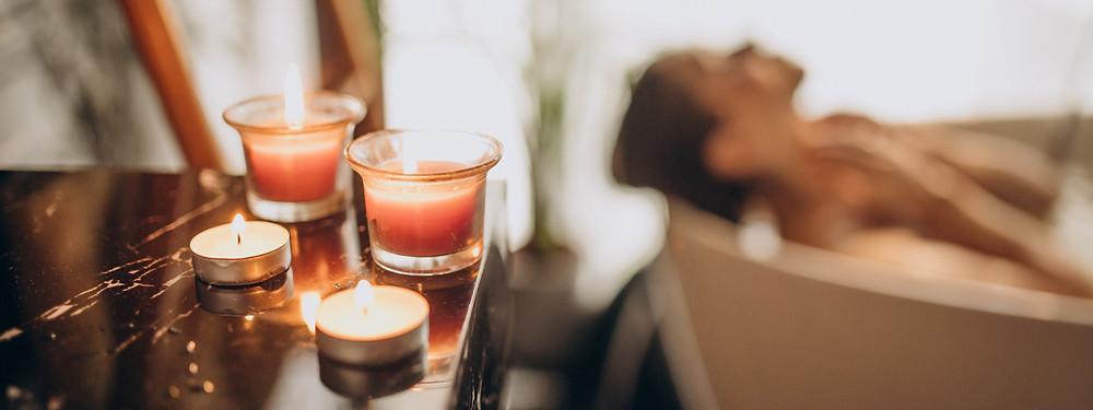 Eine Frau nimmt ein Bad mit Kerzenlicht.