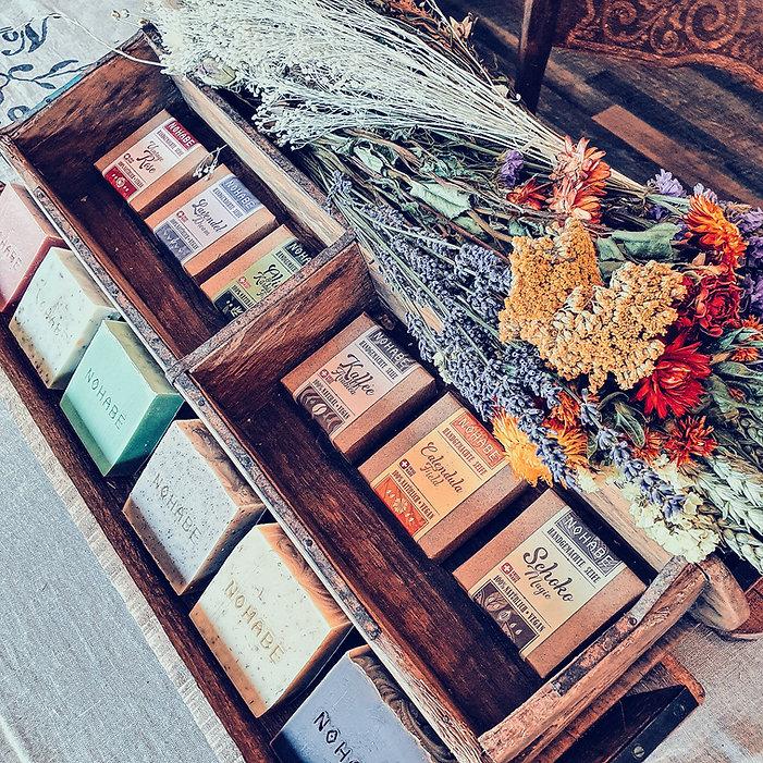 Nohabe Naturseifen in einer dekorativen Schachtel und getrocknete Blumen.