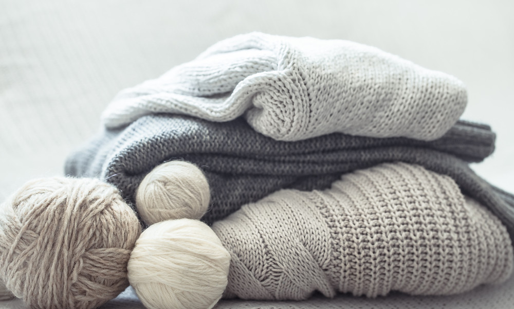 Grey wool yarns and pullovers.
