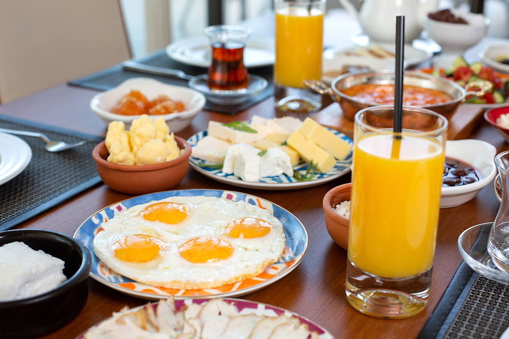 Breakfast on the table: orange juice, fried eggs, butter, cheese.