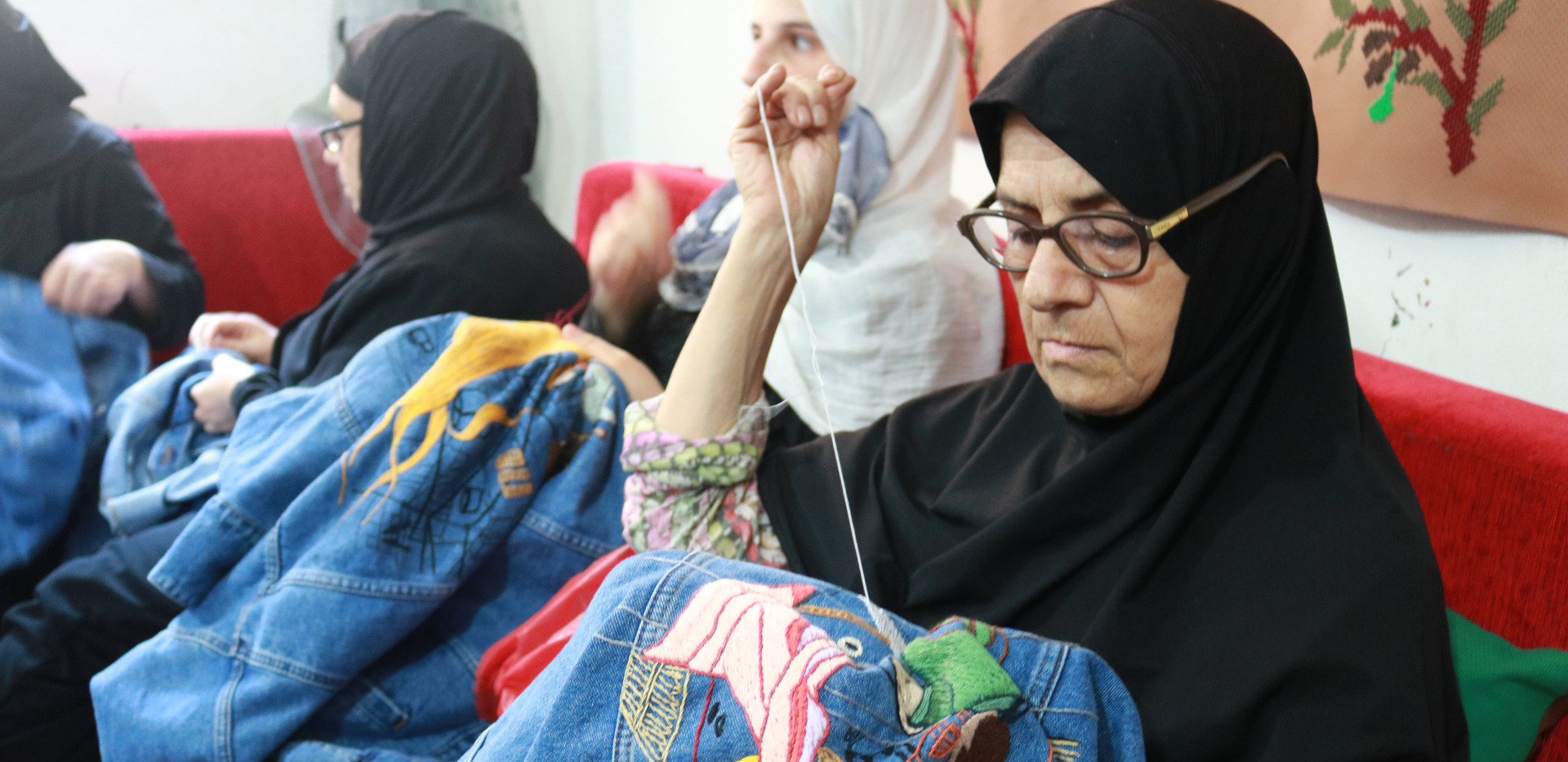 Palestinian refugee woman was sewing a pattern on a jean jacket to make a living. The pattern tells a love story that happened in Shatila.  She was born in Syria as a refugee and fled to Lebanon to seek safety after the outbreak of the Syrian civil war. .JPG