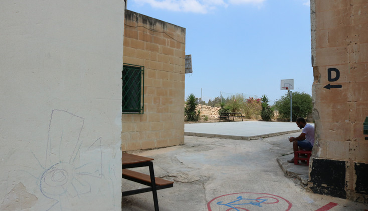 A man sitting alone at the detention center for family located in Ħal Far.