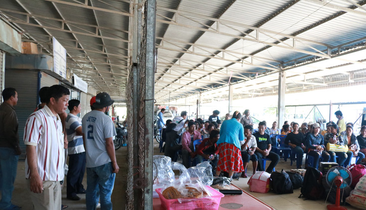 Taxi drivers were waiting outside the chain-linked fence to send migrants home. The lady in blue, also a governmental offical, provided money exchange service for migrants who just arrived in Cambodia 5 minutes ago.