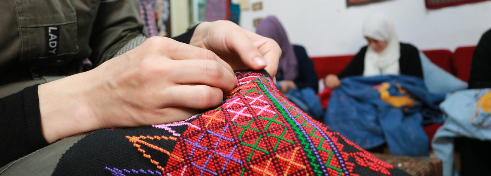 A woman was sewing a tote bag with beautiful Palestinian pattern designed by a Palestinian designer.