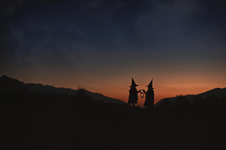 little girls dressed as witches at sunset