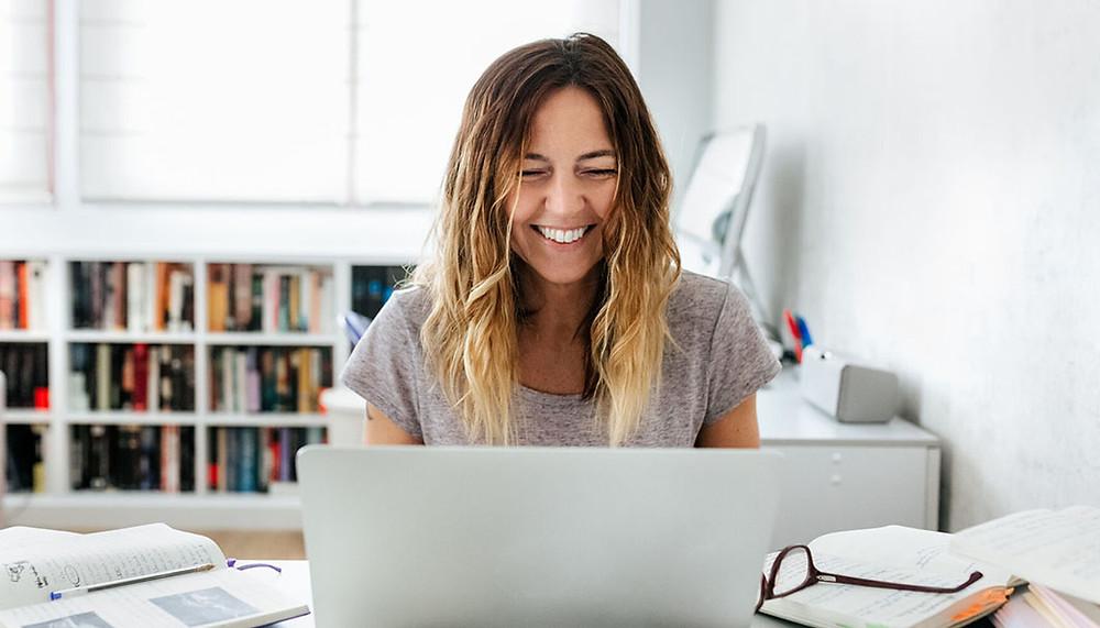 Mujer escribe su plan de negocios en su computador