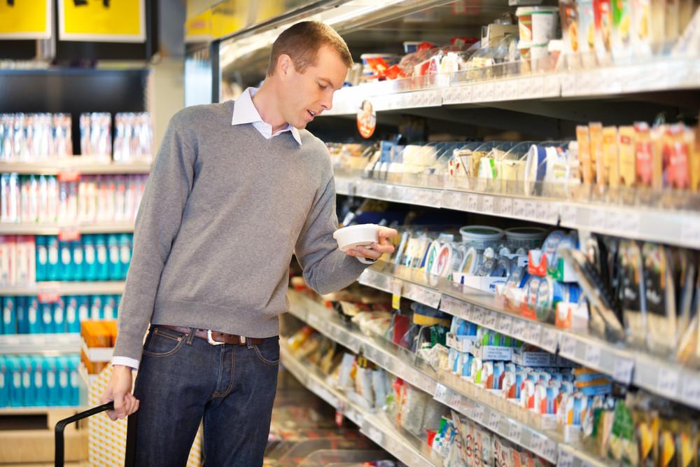 Hombre en el supermercado. Observando un producto en medio del pasillo de compras