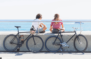 two girls sitting by the beach with their bikes parked in front of them