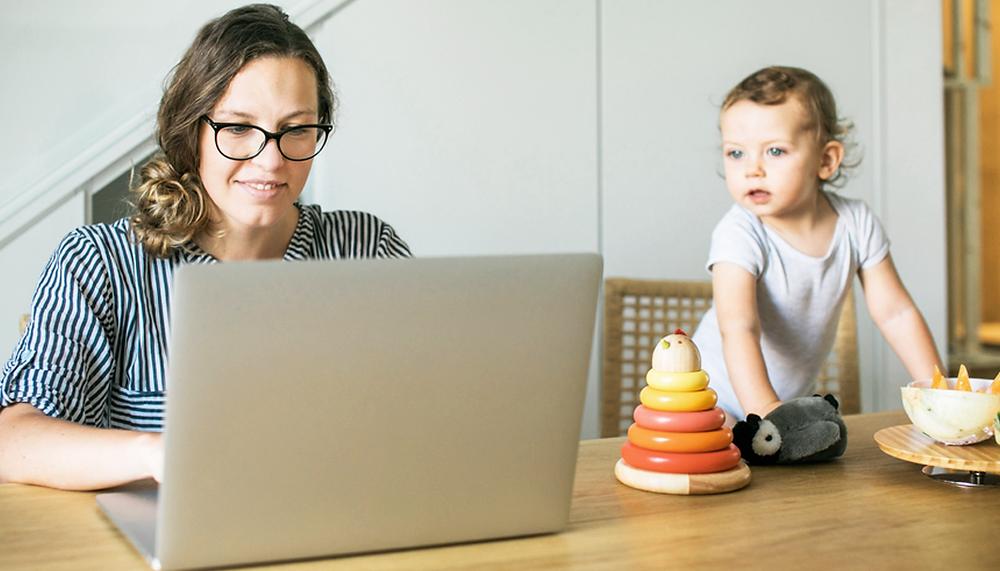 Madre trabaja en su computador ante la mirada de su bebé