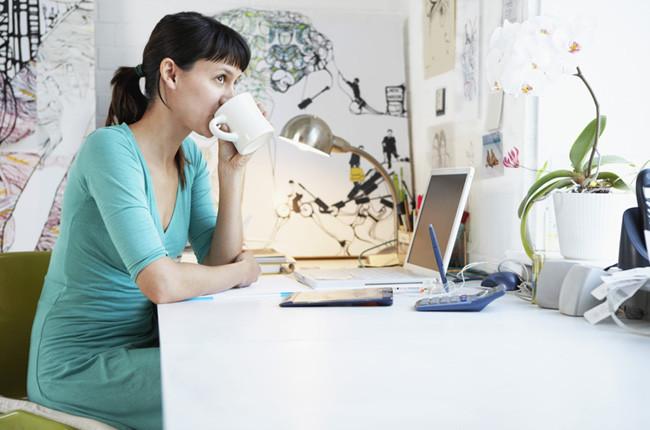 Молодая девушка с чашкой кофе у своего компьютера