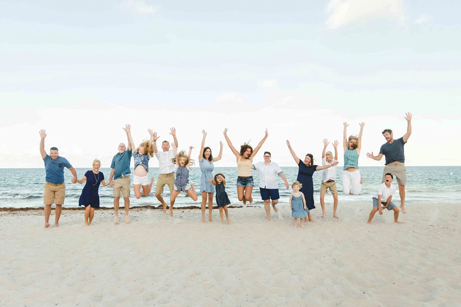 family jumping group shot on the beach