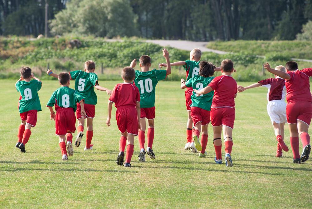 Equipo de futbol de niños. Vistos de espalda en el campo de juego. Uniforme verde con rojo