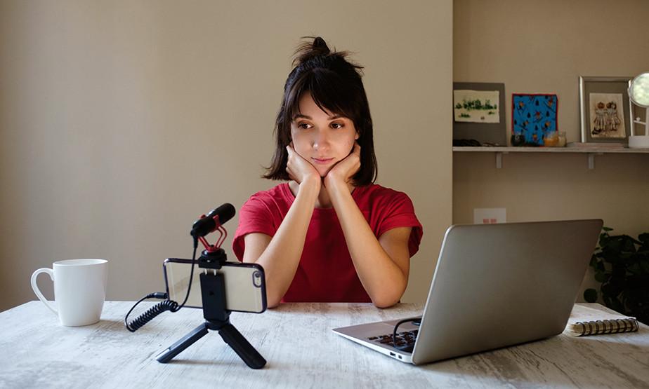 una donna seduta davanti alla telecamera che filma la creazione del suo corso online