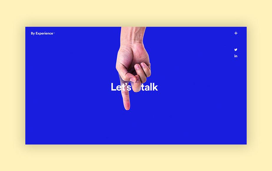"""Captura de tela do site da agência By Experience. O site tem a página inicial em azul cobalto vibrante, com uma mão fazendo sinal com o dedo indicador e o texto """"let's talk"""" em branco ao centro"""