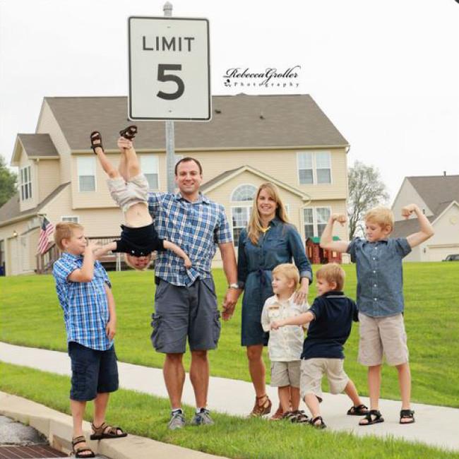 Photo d'une famille de 5 enfants devant un panneau 5
