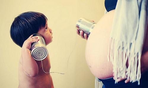 Madre embarazada e hijo mayor escuchan con latas la panza