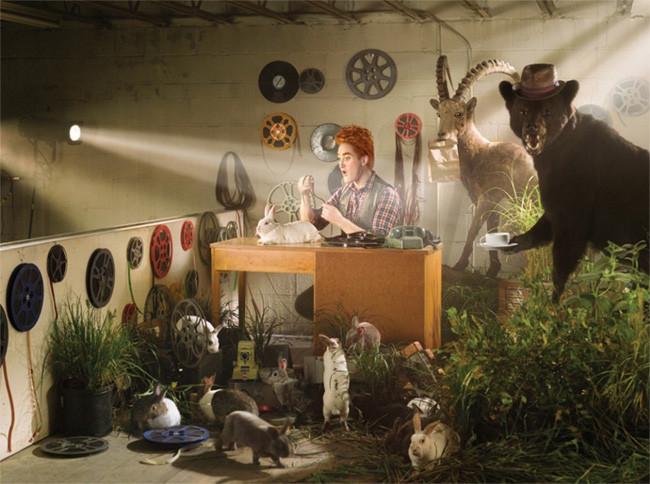 Hombre escribiendo en un escritorio rodeado de un oso y un alce