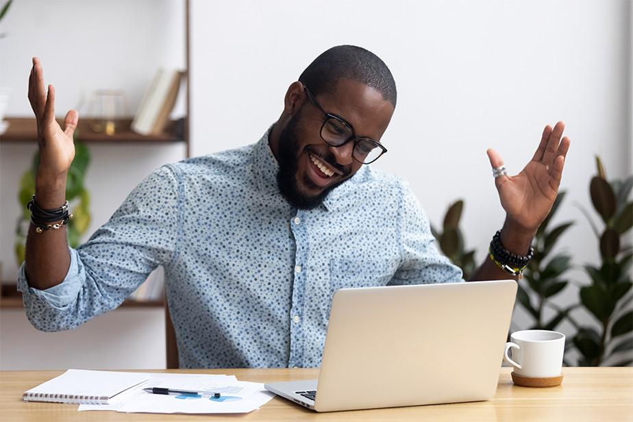 Hombre con gestos de felicidad frente a su computador