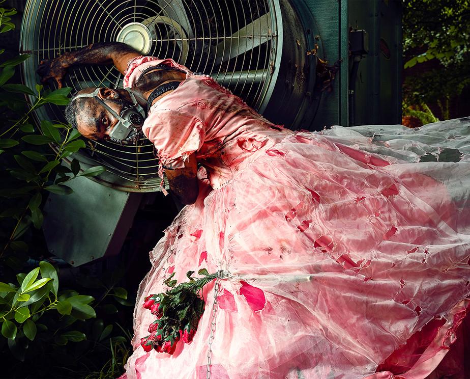 Sesja zdjęciowa w pomieszczeniach - surrealistyczny portret mężczyzny w różowej sukience i masce gazowej