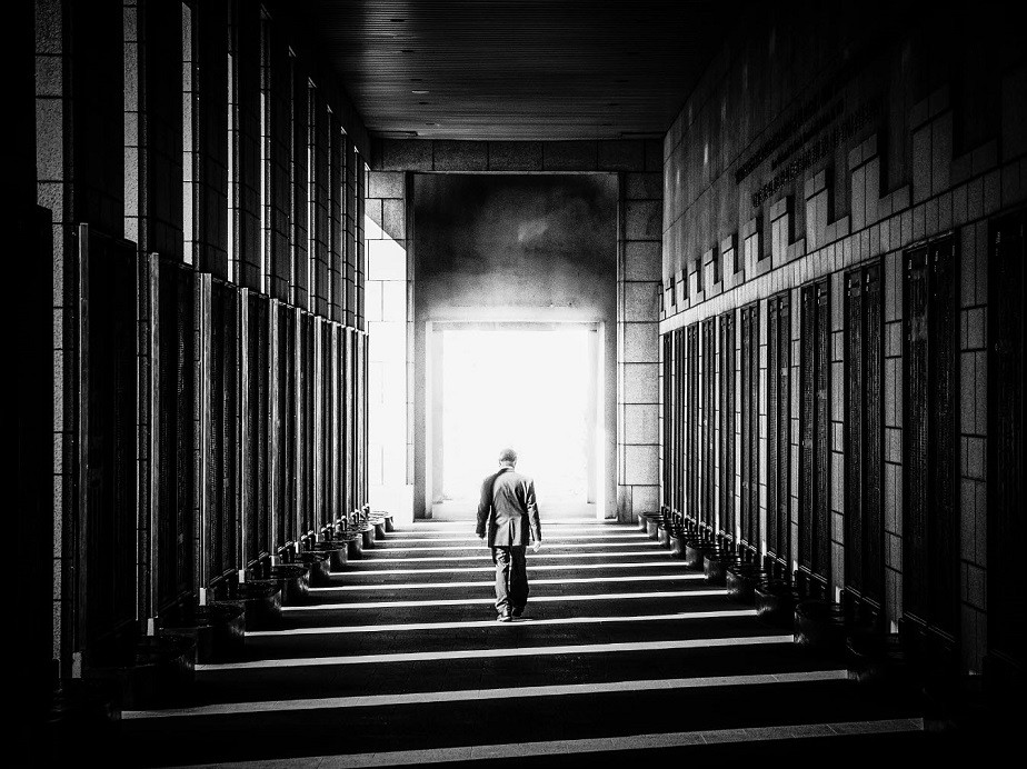 Black and white picture of a man walking in a corridor by Wix landscape photographer Albert Dros