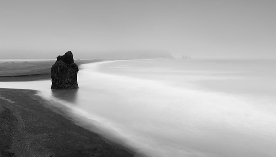 black and white long exposure of empty beach shore