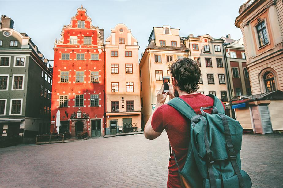 아름다운 빌딩 외관을 카메라로 담고 있는 빨간 티셔츠를 입은 남자 이미지