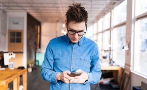 мужчина проверяющий рабочую почту на телефоне
