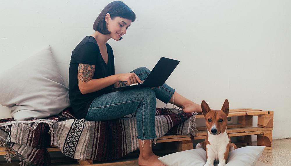 Junge Frau mit Laptop und Hund sitzt auf einem Sofa und sammelt Geschäftsideen