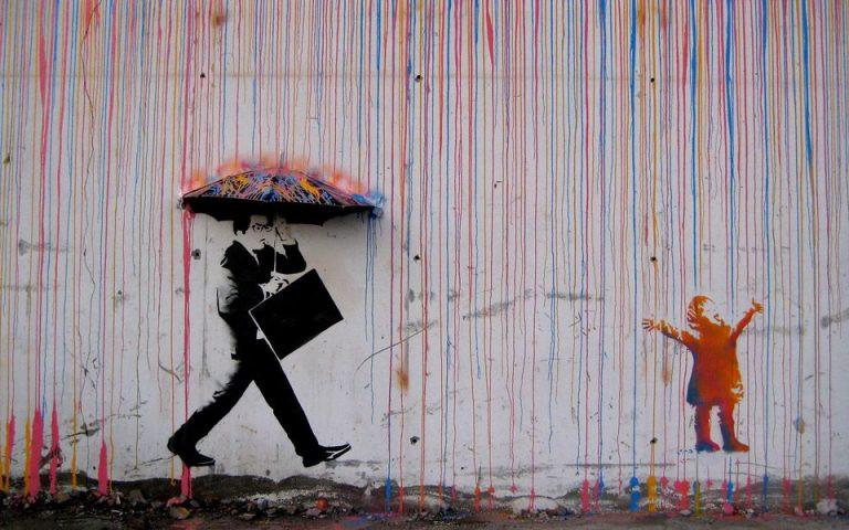 雨の日に男性が歩いているストリートアート