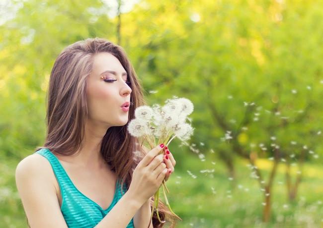 Jeune femme qui souffle sur une fleur