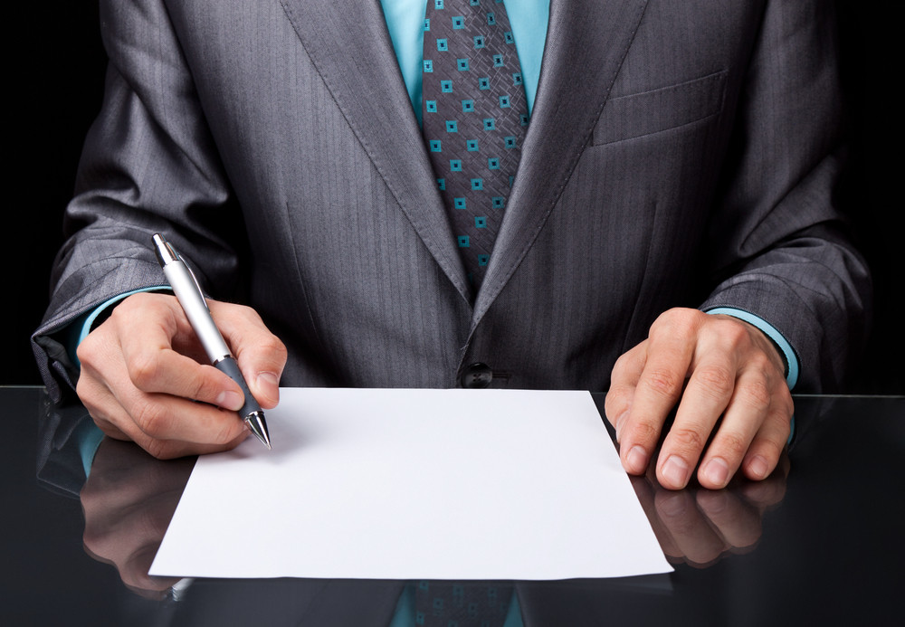 Hombre firmando un papel en blanco