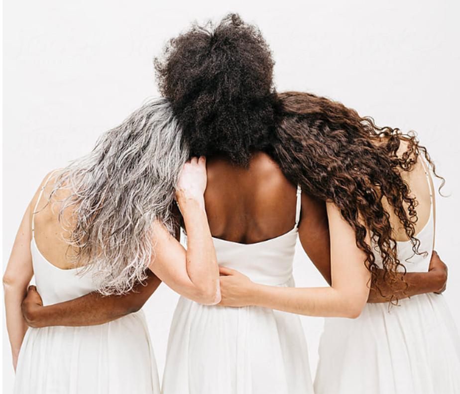 Drie vrouwen in witte jurken in een rij met de armen om elkaar heen geslagen.