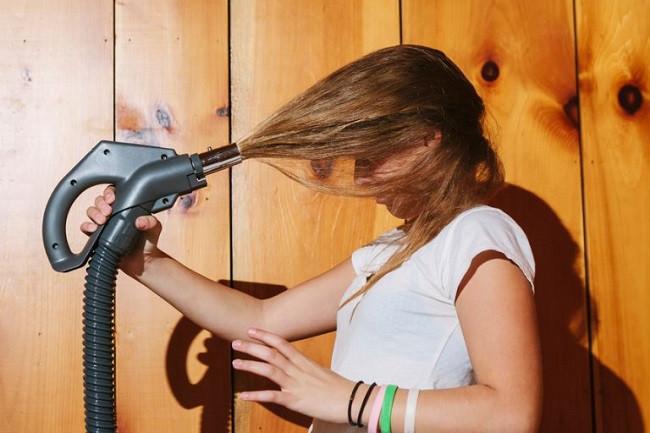 Femme qui se coiffe avec un aspirateur