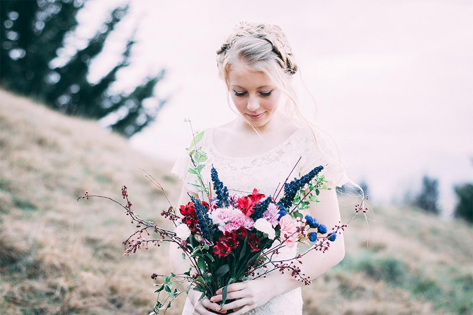 Fotografía de novia posando en el campo con ramo de flores colorido