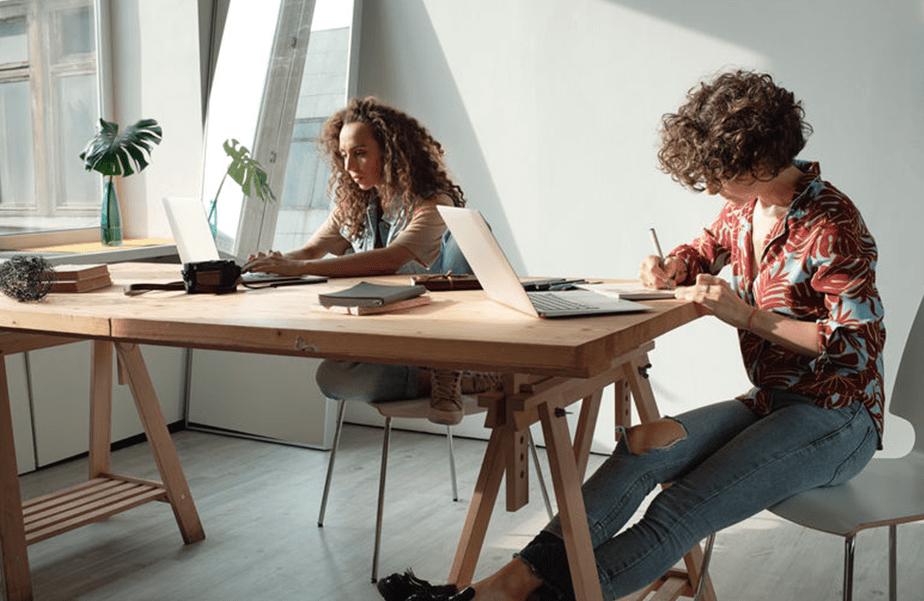 Zwei Mitarbeiterinnen am Schreibtisch mit Computer in sonnigem Büro