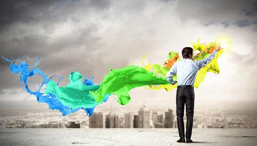 Бизнесмен рисует красками на фоне серого городского пейзажа
