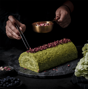 a cook putting dried flowers on top of a green cake